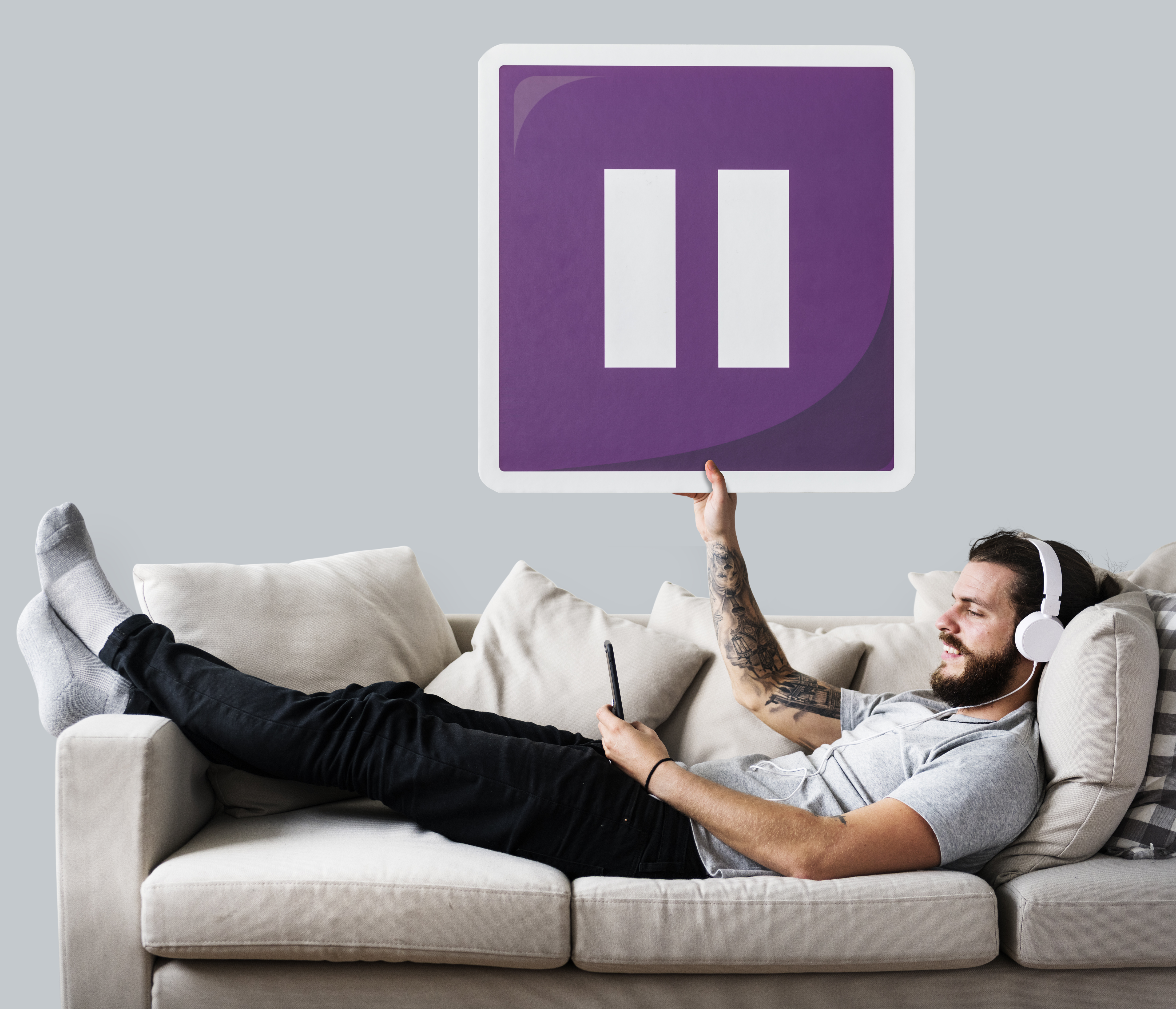 Male On A Couch Holding A Pause Button Icon